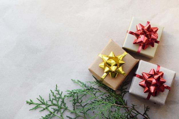 Diy weihnachtsgeschenkboxen mit schleifen zu hause. kästen mit geschenken auf einem hintergrund des bastelpapiers und eines zweigs der tanne Premium Fotos