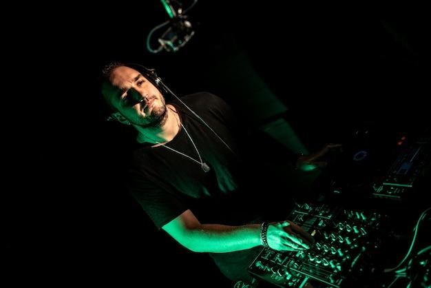Dj spielt house- und technomusik in einem nachtclub. musik mischen und steuern. Premium Fotos