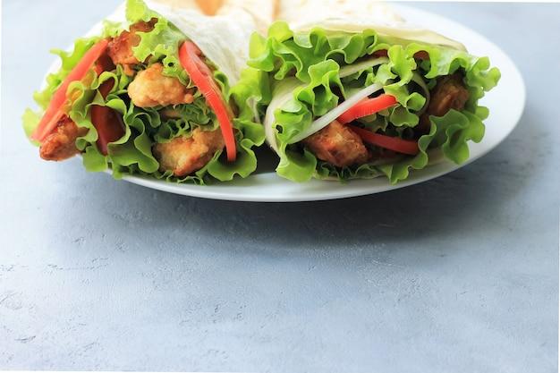 Döner auf einem weißen teller. shawarma mit fleisch, zwiebeln, salat und tomate an auf grauem hintergrund. Premium Fotos