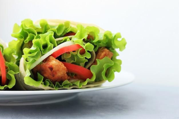 Döner auf einem weißen teller. shawarma mit fleisch, zwiebeln, salat und tomate auf grauem hintergrund. Premium Fotos