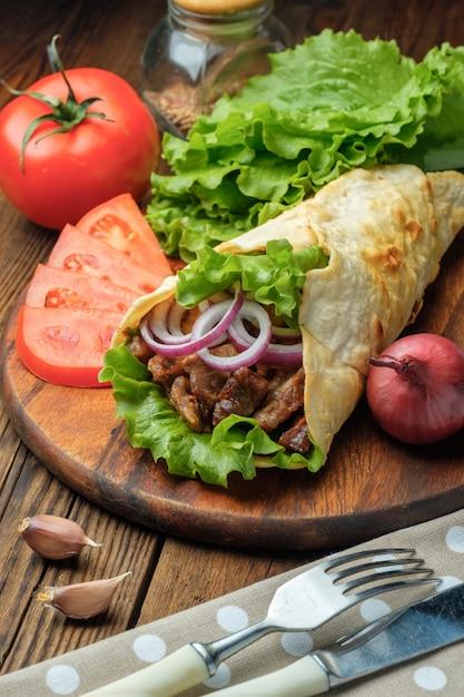 Döner liegt auf dem schneidebrett. shawarma mit fleisch, zwiebeln, salat liegt auf einem weißen alten holztisch. Premium Fotos