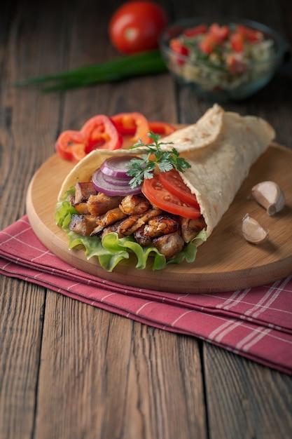Döner liegt auf dem schneidebrett. shawarma mit hühnerfleisch, zwiebeln, salat liegt auf einem dunklen alten holztisch. Premium Fotos
