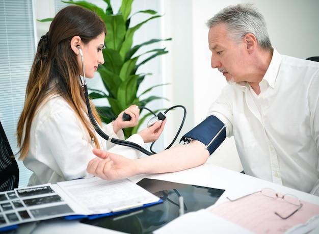 Doktor checking blutdruck eines patienten Premium Fotos