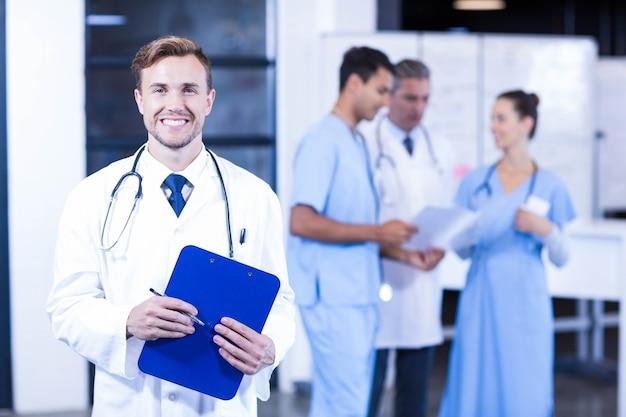 Doktor, der ärztlichen attest hält und während seine kollegendiskussion lächelt Premium Fotos