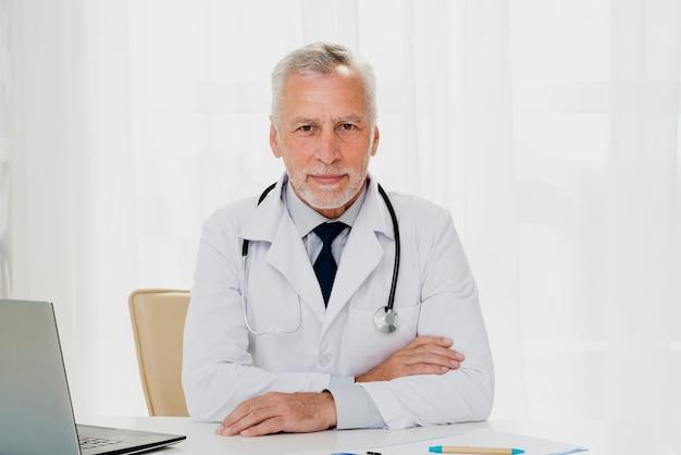Doktor, der am schreibtisch sitzt Premium Fotos