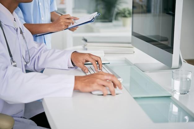 Doktor, der an computer arbeitet Kostenlose Fotos
