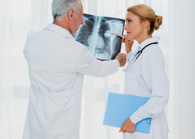 Doktor, der auf schrittmacher auf röntgenstrahl zeigt Kostenlose Fotos