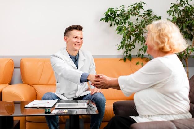 Doktor, der auf sofa sitzt und geduldige hand hält Kostenlose Fotos