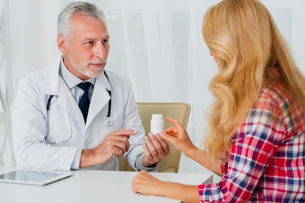 Doktor, der dem patienten medikation übergibt Kostenlose Fotos