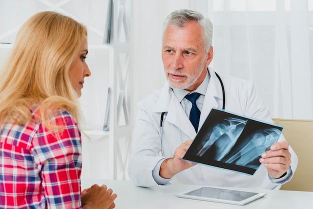 Doktor, der dem patienten röntgenstrahl zeigt Kostenlose Fotos