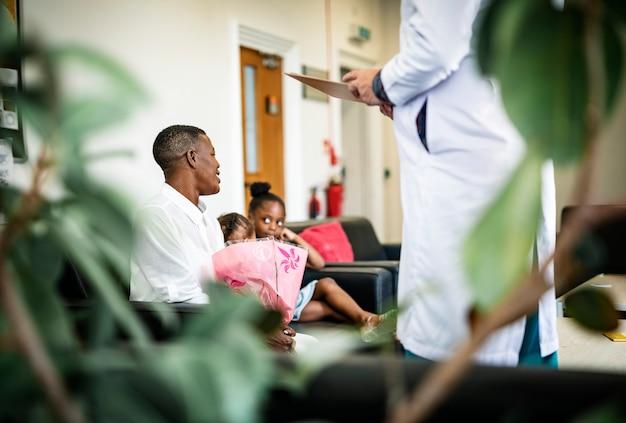 Doktor, der den verwandten im warteraum gute nachrichten gibt Premium Fotos