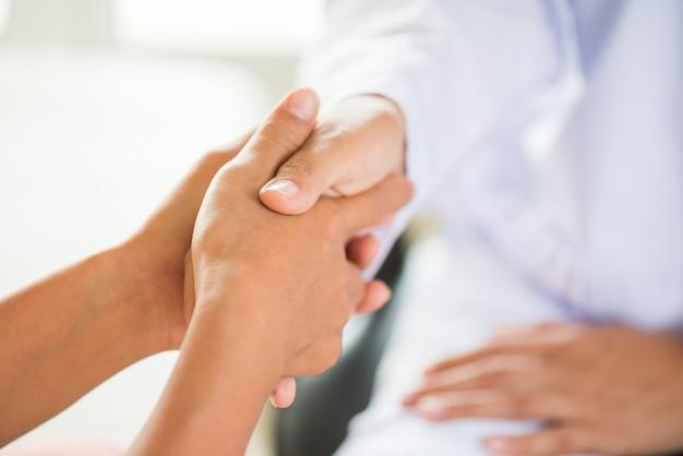 Doktor, der die hand des patienten hält. medizin und gesundheits-konzept. Premium Fotos