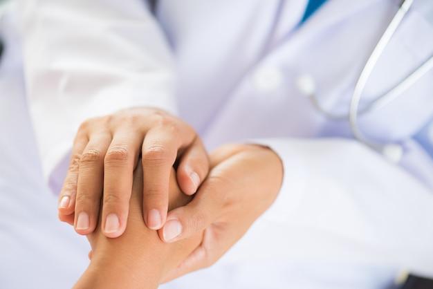 Doktor, der die hand des patienten hält. medizin und gesundheits-konzept Premium Fotos