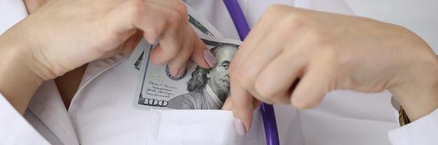 Doktor, der dollarschein in uniformtasche bei kliniknahaufnahme steckt Premium Fotos