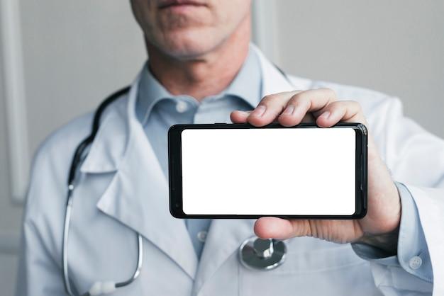 Doktor, der ein handy zeigt Kostenlose Fotos
