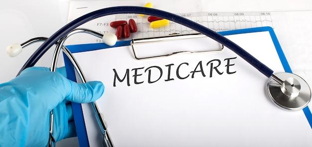 Doktor, der eine karte mit text medicare, medizinisches konzept hält Premium Fotos