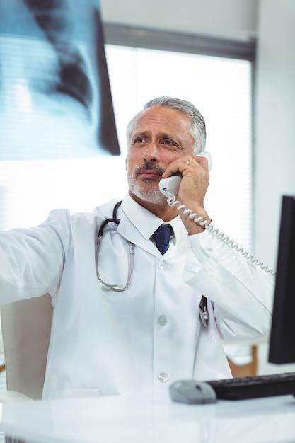 Doktor, der einen röntgenstrahlbericht bei der unterhaltung am telefon an der klinik überprüft Premium Fotos