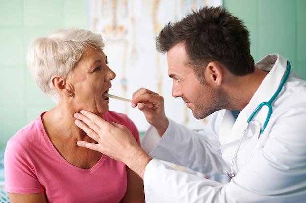 Doktor, der hals der älteren frau prüft Kostenlose Fotos