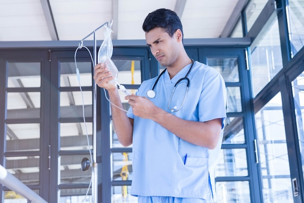 Doktor, der intravenösen tropfenfänger im krankenhaus überprüft Premium Fotos