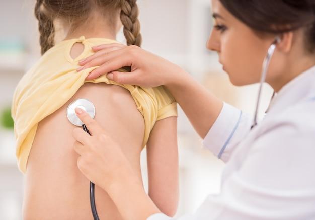 Doktor, der kleines mädchen mit stethoskop überprüft. Premium Fotos