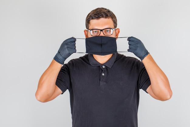 Doktor, der maske im schwarzen poloshirt trägt und ernst schaut Kostenlose Fotos