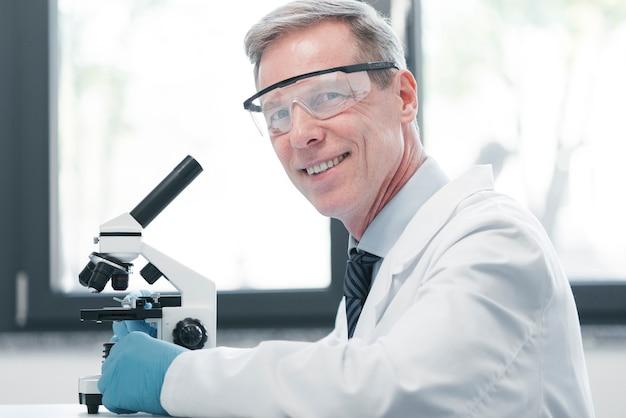 Doktor, der mit einem mikroskop analysiert Kostenlose Fotos