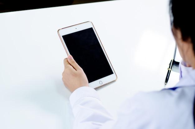 Doktor, der mit laptop-computer arbeitet und auf schreibarbeit schreibt. krankenhaus hintergrund Premium Fotos