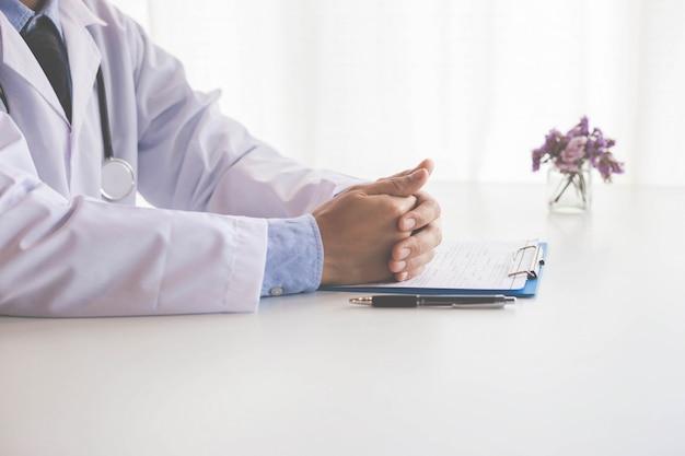 Doktor, der mit laptop-computer arbeitet und auf schreibarbeit schreibt. krankenhaus hintergrund. Premium Fotos