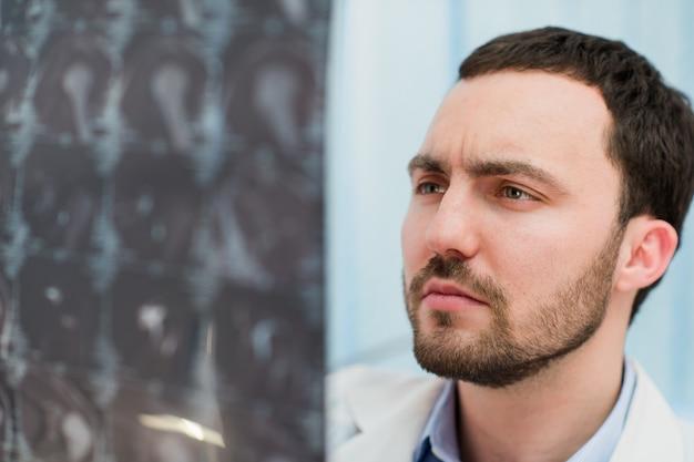 Doktor, der mri röntgenstrahl des gehirns im büro ansieht Premium Fotos