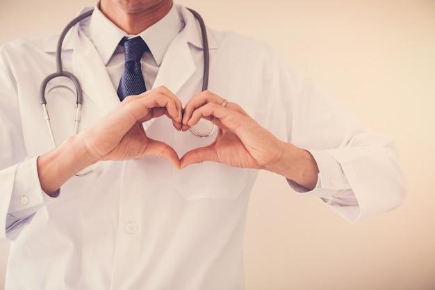 Doktor, der seine hände in der herzform, herzgesundheit, krankenversicherungskonzept macht Premium Fotos