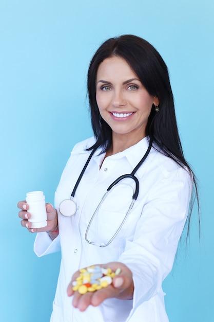 Doktor, der weiße robe und stethoskop hält, die pillen halten Kostenlose Fotos