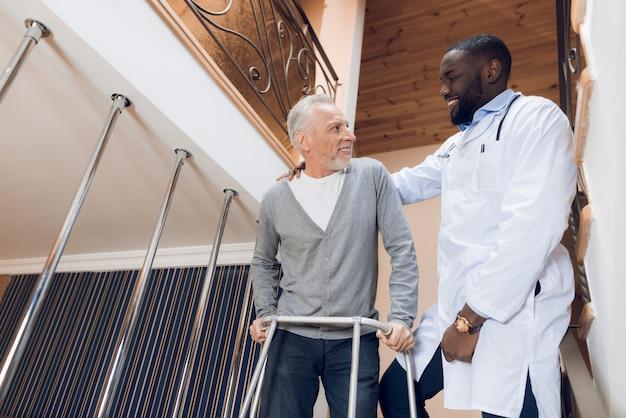 Doktor hilft einem mann, die treppe in einem pflegeheim hinunterzugehen. Premium Fotos