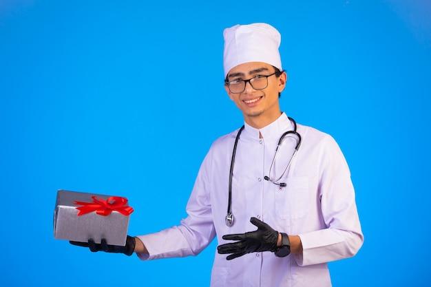 Doktor in der weißen medizinischen uniform, die eine geschenkbox hält und zur kamera schaut. Kostenlose Fotos