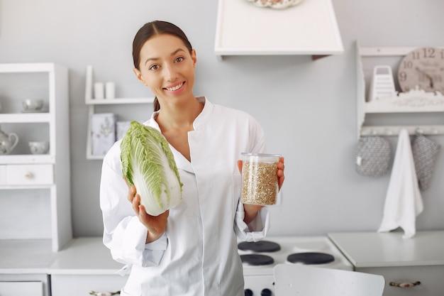 Doktor in einer küche mit gemüse Kostenlose Fotos