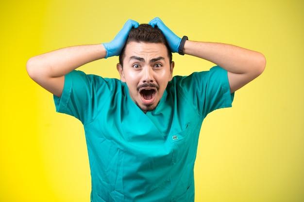 Doktor in grüner uniform und handmaske umarmt seinen kopf und schreit. Kostenlose Fotos