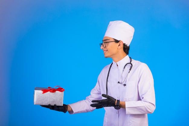 Doktor in weißer medizinischer uniform, die eine geschenkbox hält und sich bei jemandem bedankt. Kostenlose Fotos