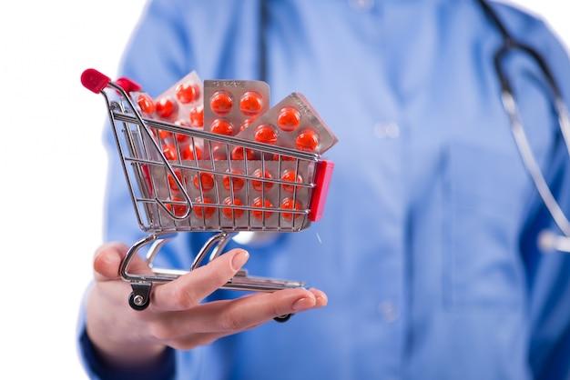 Doktor mit dem einkaufswagen voll von den pillen getrennt auf weiß Premium Fotos
