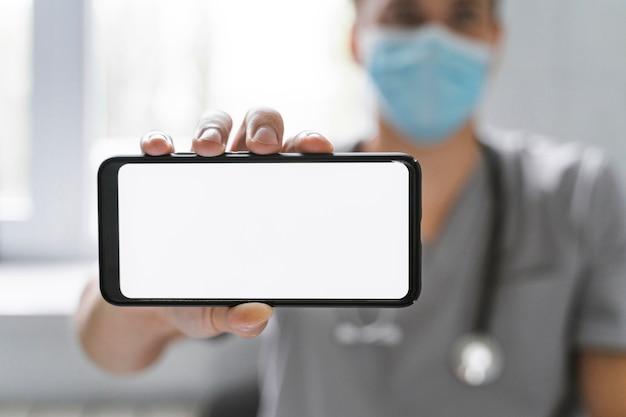 Doktor mit medizinischer maske, die smartphone hält Kostenlose Fotos