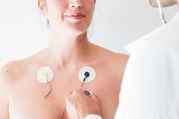 Doktor mit stethoskop nahe frau mit elektroden Kostenlose Fotos