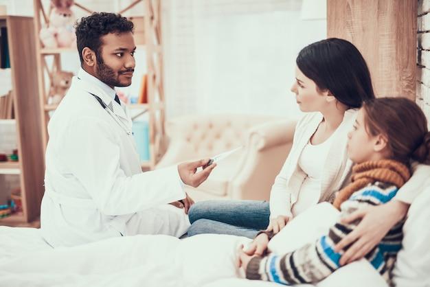 Doktor nimmt temperatur des mädchens mit schwangerer mutter. Premium Fotos