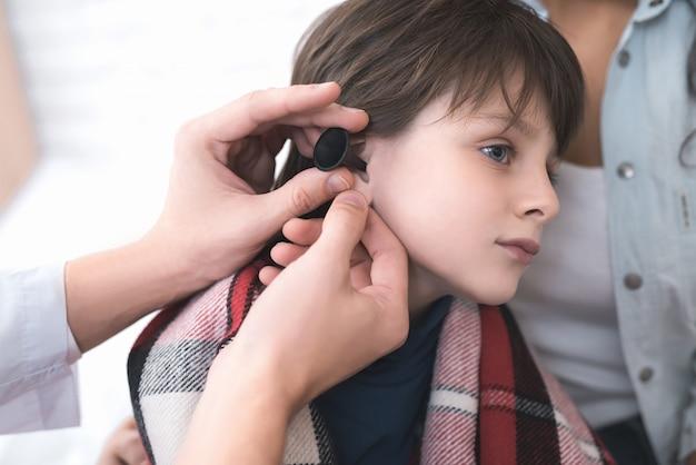 Doktor überprüft das ohr eines kranken jungen. Premium Fotos