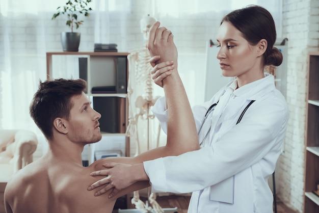 Doktor überprüft den arm des athleten im krankenhauszimmer Premium Fotos