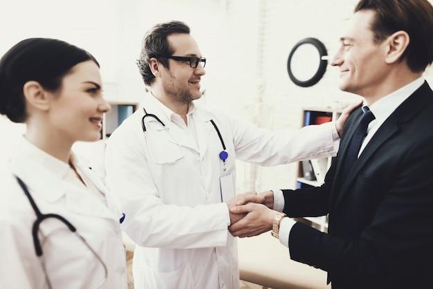 Doktor und patient ist händeschütteln in der klinik. Premium Fotos
