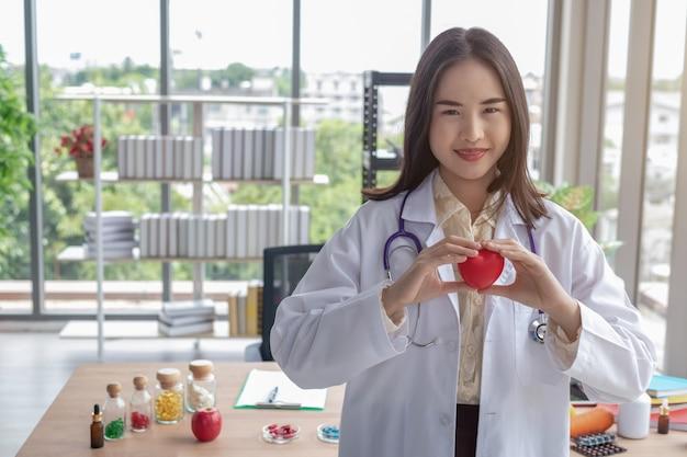 Doktor zeigt ein rotes herz im büro Premium Fotos
