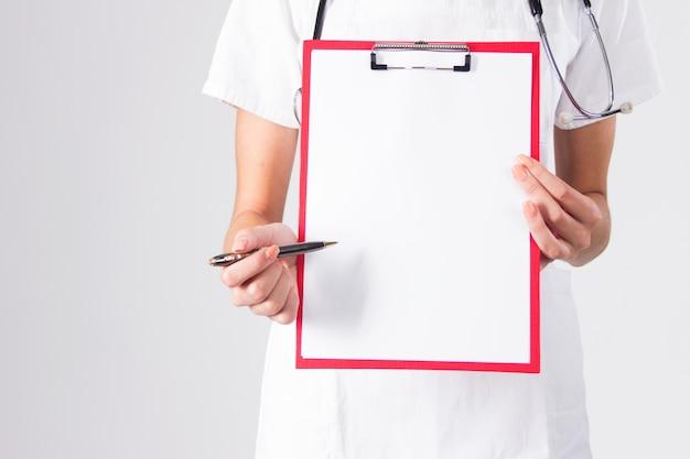 Doktor zeigt leere Zwischenablage mit Stift auf einem weißen Hintergrund isoliert. Kostenlose Fotos