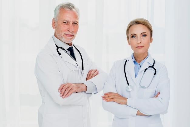 Doktoren, die kamera mit den händen gekreuzt betrachten Kostenlose Fotos