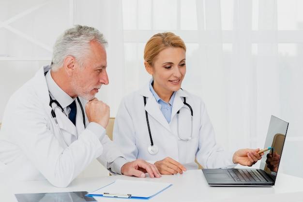 Doktoren, die laptop beim sitzen betrachten Kostenlose Fotos