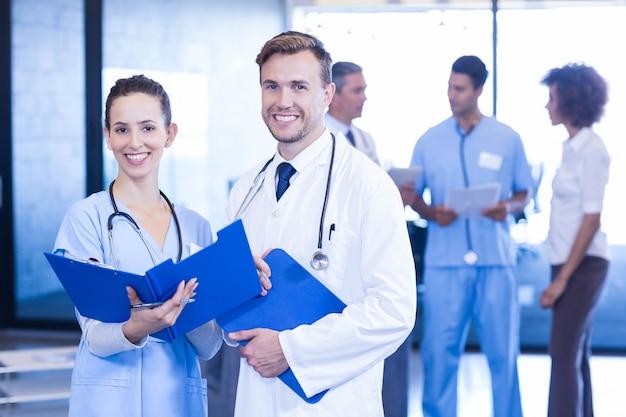 Doktoren mit dem ärztlichen attest, der im krankenhaus schaut und lächelt Premium Fotos