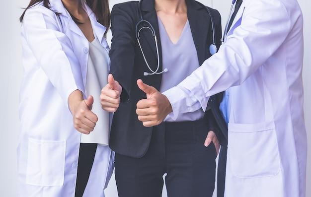 Doktoren und krankenschwestern koordinieren hände. doktoren daumen oben, konzept-teamwork Premium Fotos