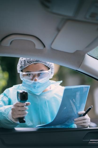 Doktorfrau verwenden infrarot-stirn-thermometer-pistole, um die körpertemperatur zu überprüfen. für virus-covid-19-symptome. frau mit dem isolationskleid oder den schutzanzügen und den chirurgischen gesichtsmasken im freien. Kostenlose Fotos